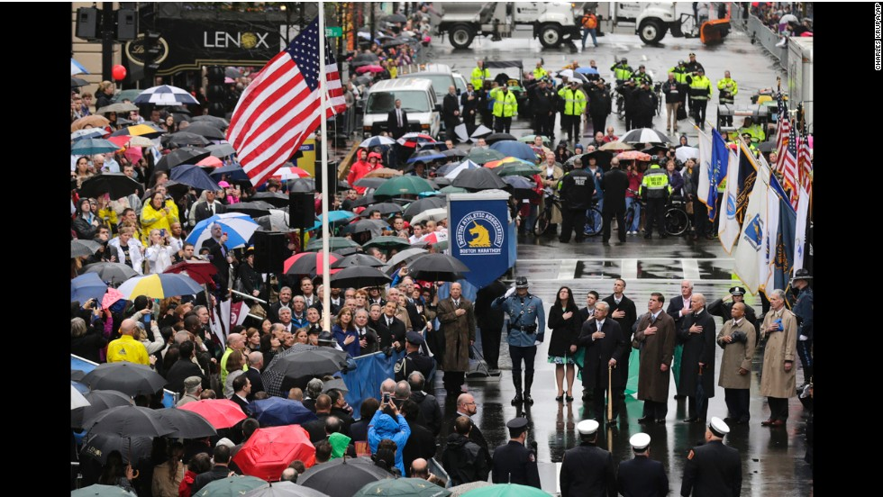 People pause Tuesday, April 15, as the American flag is raised at the finish line of the Boston Marathon, where two homemade bombs went off one year ago. It was the deadliest terrorist attack in the United States since 9/11.