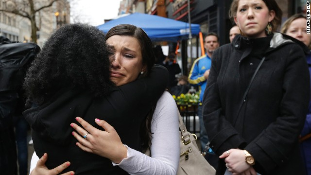 Olivia Savarino, facing the camera, hugs Christelle Pierre-Louis during the ceremonies on Boylston Street. Savarino was working at the Forum restaurant when a bomb went off in front of the building on April 15, 2013.