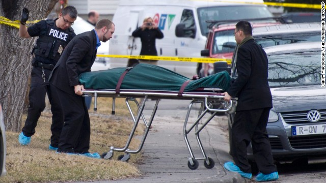 Police remove a body from the scene of a multiple fatal stabbing in northwest Calgary, Alberta.