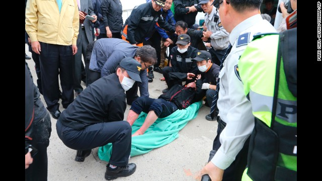 Police and rescue teams carry a passenger at the port in Jindo on April 16.