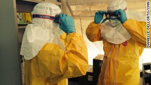 Drs. Sanjay Gupta, left, and Tim Jagatic don isolation gear outside an Ebola ward in Conakry, Guinea.