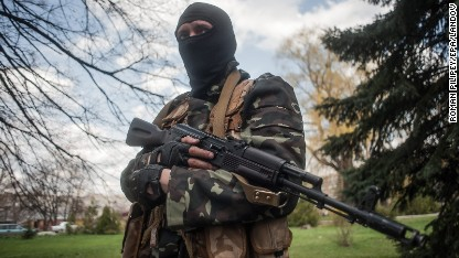 A masked gunman stands guard near tanks in Slaviansk, Ukraine, on Wednesday, April 16.