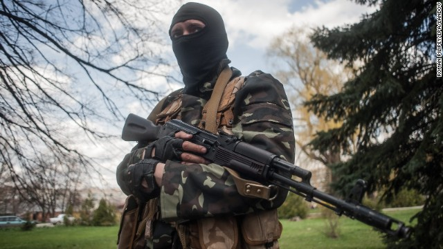 A masked gunman stands guard near tanks in Slavyansk, Ukraine, on Wednesday, April 16.