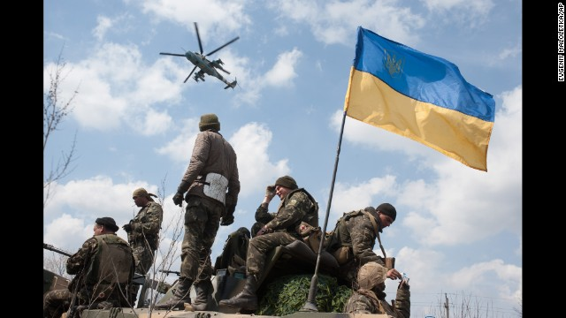 A Ukrainian helicopter flies over a column of Ukrainian Army combat vehicles on the way to Kramatorsk, a city in eastern Ukraine, on April 16.