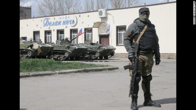 A masked pro-Russian gunman guards combat vehicles parked in downtown Slovyansk on April 16.