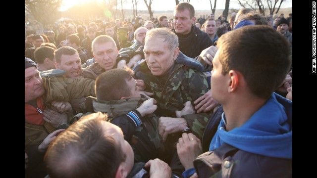Ukrainian Gen. Vasily Krutov is surrounded by protesters after addressing the crowd outside an airfield in Kramatorsk on Tuesday, April 15.