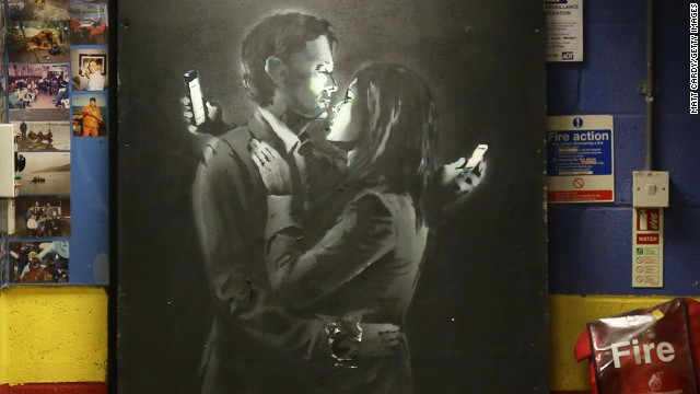 "Banksy appears on black wooden board at a youth center in Bristol, England, on Wednesday, April 16. Called ""Mobile Lovers,"" it features a couple embracing while checking their cell phones. Members of the youth center took down the piece from a wall on a Bristol street and replaced it with a note saying the work was being held at the club ""to prevent vandalism or damage being done."" The discovery came shortly after another image believed to be by Banksy surfaced in Cheltenham, England."