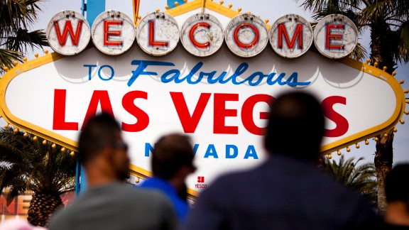 "People pass in front of the ""Welcome to Las Vegas"" sign in Las Vegas, Nevada, U.S., on Thursday, March 20, 2014. The average gambling budget of Las Vegas visitors rose 10 percent to $530 last year, the biggest increase since 2005, according to a study released on March 21 by the citys convention and visitors authority. Photographer: Sam Hodgson/Bloomberg via Getty Images"