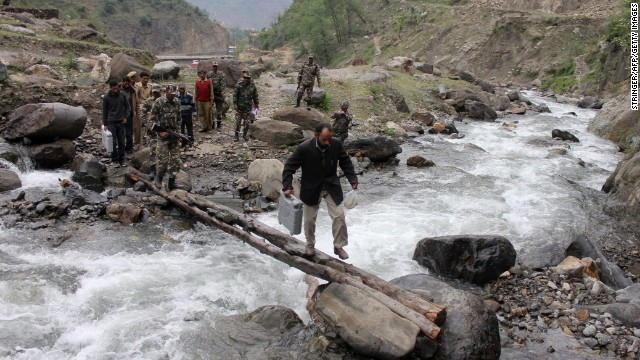 An election official carries an electronic voting machine across a makeshift bridge after picking it up from a distribution center in Doda on April 16.