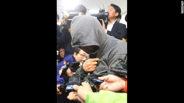 The ship's captain, Lee Joon Suk, arrives at the Mokpo Police Station in Mokpo on April 17. His head and face covered, he broke down in tears when reporters asked whether he had anything to say.