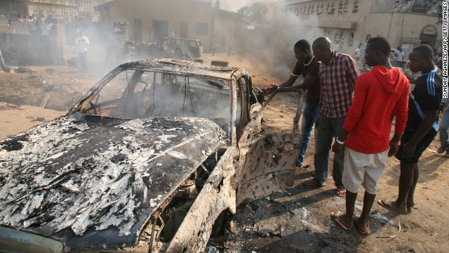 "Men look at the wreckage of a car after a bomb blast at St. Theresa Catholic Church outside Abuja on December 25, 2011. A string of bombs struck churches in five Nigerian cities, leaving dozens dead and wounded on the Christmas holiday, authorities and witnesses said. Boko Haram's targets included police outposts and churches as well as places associated with ""Western influence."""