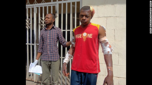 A paramedic helps a young man injured during one of the multiple explosions and shooting attacks as he leaves a hospital in the northern city of Kano on January 21, 2012. A spate of bombings and shootings left more than 200 people dead in Nigeria's second-largest city. Three days later, a joint military task force in Nigeria arrested 158 suspected members of Boko Haram.