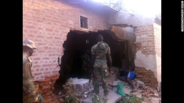 A soldier stands in front of a damaged wall and the body of a prison officer killed during an attack on a prison in the northeastern town of Bama on May 7, 2013. Two soldiers were killed during coordinated attacks on multiple targets. Nigeria's military says more than 100 Boko Haram militants carried out the attack.