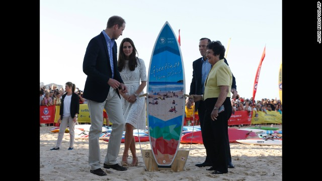 William and Catherine receive a surfboard alongside Australian Prime Minister Tony Abbott and Manly Mayor Jean Hay at Manly Beach.
