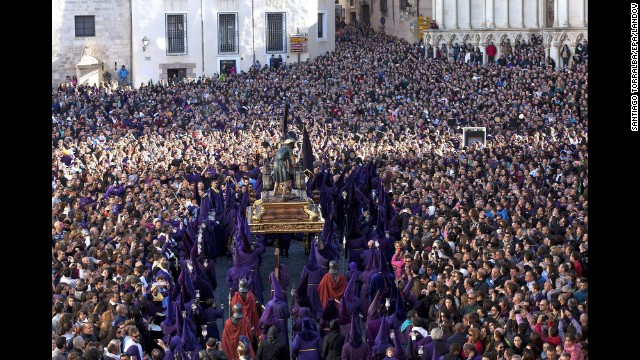 "Penitents, surrounded by several thousand people in Cuenca, Spain, carry the statue of Our Father Nazarene during the Good Friday procession ""Way of Calvary."""