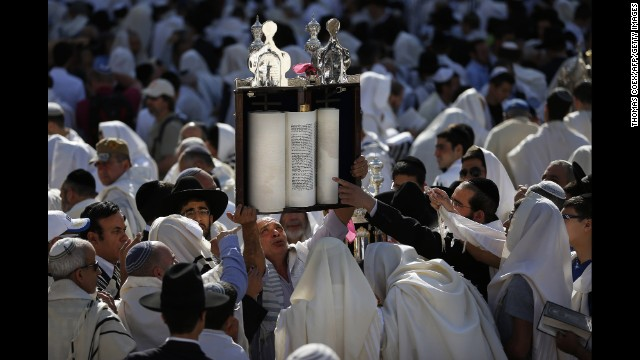 A man raises Torah scrolls during the Cohanim prayer at the Western Wall on April 17.