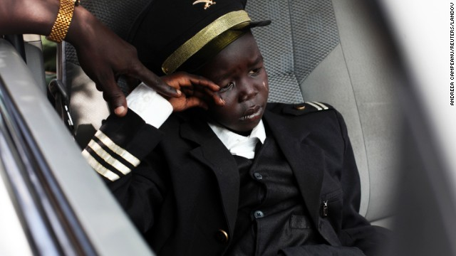An 8-year-old boy waits in a car during Petroleum Minister Stephen Dhieu Dau's visit to an oil production facility in Paloch, South Sudan, on Sunday, March 2. The boy's father, a member of the Sudan People's Liberation Army, said his son was dressed like a pilot because that's what he wants to be when he grows up.