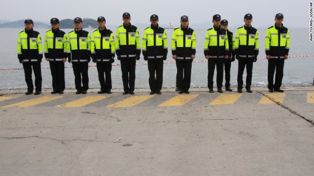 Police officers stand guard Saturday, April 19, at the port in Jindo to prevent relatives of the ferry's missing passengers from jumping in the water. Some relatives have said they will swim to the shipwreck site and find their missing family members by themselves.