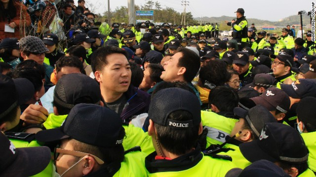 Relatives of missing passengers aboard the sunken ferry struggle with policemen as they try to march toward the presidential house to protest the government's rescue operation at a port in Jindo, South Korea, on Sunday, April 20. The ferry sank Wednesday, April 16, as It was headed to the resort island of Jeju from the port of Incheon.