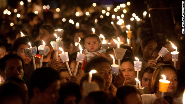 Roman Catholic devotees attend an Easter Mass outside St. Domingo Church in Manila, Phillipines.