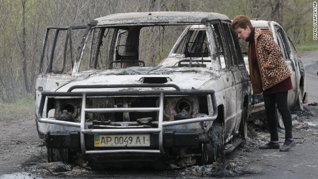 A resident inspects burnt-out cars at the roadblock on April 20.