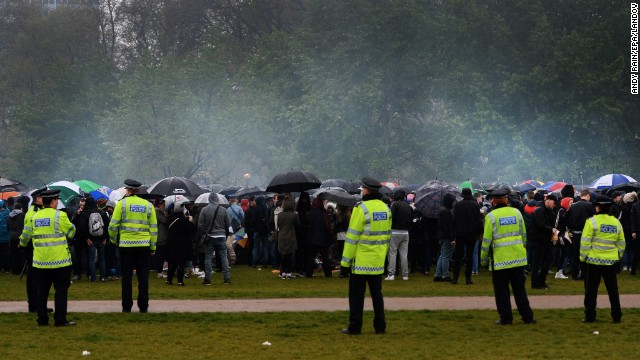 British police look on as a cloud of smoke rises over protesters in London's Hyde Park.