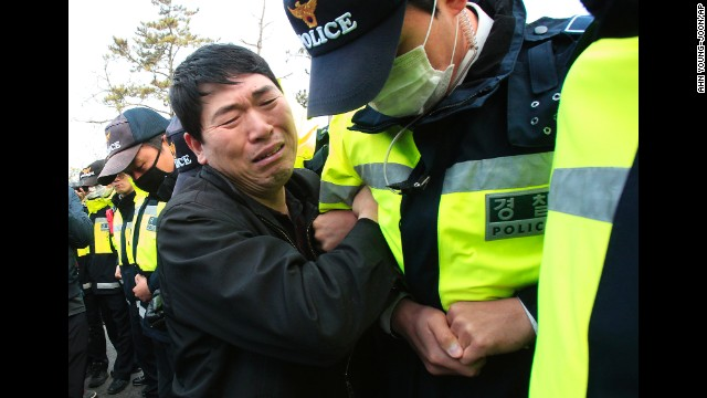 A relative of a missing passenger struggles with a policeman as he tries to march toward the presidential house in Jindo on April 20 to protest the government's rescue operation.