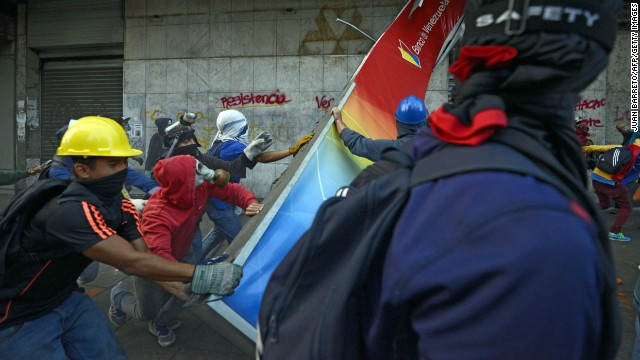Demonstrators destroy a bank sign during a protest against the government of Venezuelan President Nicolas Maduro in Caracas on Sunday, April 20. For months, protesters unhappy with Venezuela's economy and rising crime have been at odds with security forces.