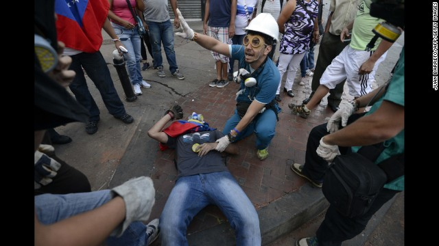 A man helps an injured demonstrator in Caracas on April 20.