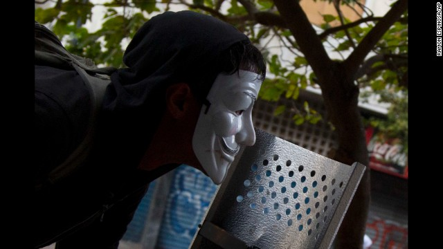 A masked protester watches clashes with the National Police in Caracas on Thursday, April 17.