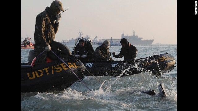 Search personnel dive into the waters of the Yellow Sea off the coast of South Korea near the sunken ferry Sewol on Wednesday, April 23. More than 100 people have died and many are missing after the ferry sank on Wednesday, April 16, as it was headed to the resort island of Jeju from the port of Incheon.