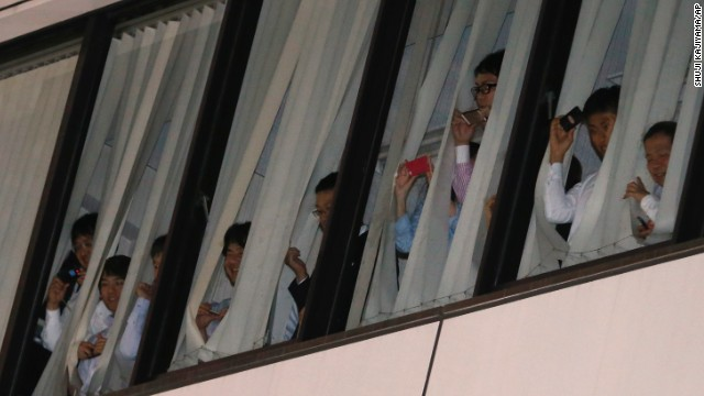 Office workers try to catch a glimpse of Obama as he and Japanese Prime Minister Shinzo Abe have dinner in Tokyo's Ginza District on Wednesday, April 23.