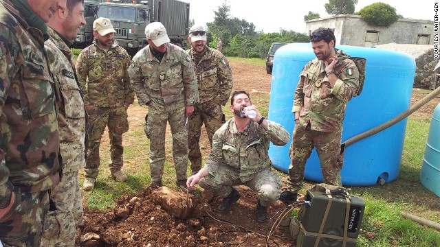 Pictured, an Italian soldier drinks water filtered through the Spring system.