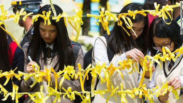 Schoolchildren tie yellow ribbons onto the roadside of a main gate at Danwon High School on April 24, 2014.