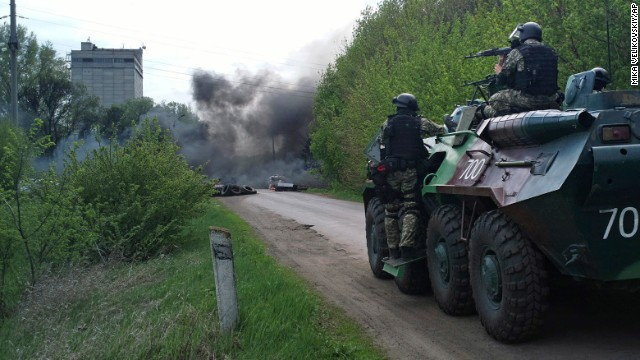Ukrainian troops take position near burning tires at a pro-Russian checkpoint in Slavyansk following an attack by Ukrainian soldiers on Thursday, April 24.