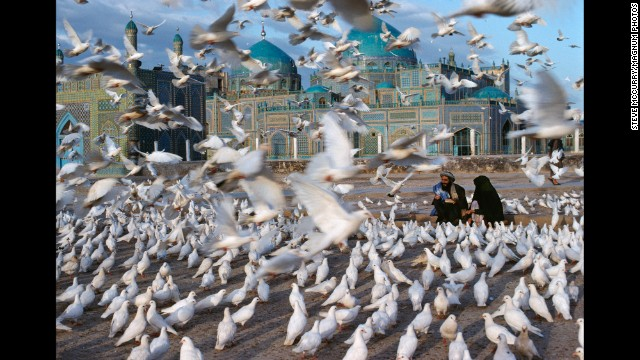 Doves fly in front of the Blue Mosque in Mazar-i-Sharif, 1992. See what inspires iconic photographer Steve McCurry.