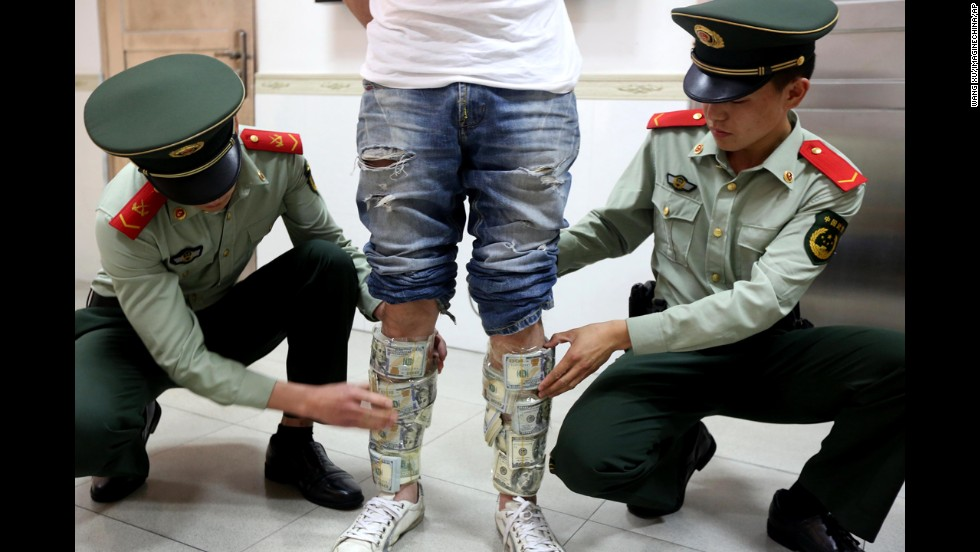 Officers reveal U.S. banknotes strapped to the legs of a man at a checkpoint in the Chinese city of Shenzhen on Wednesday, April 23. The man hid around $580,000 in excess cash.