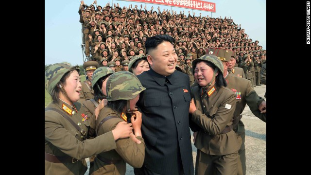 In this photo released Thursday, April 24, by the state-run Korean Central News Agency, North Korean leader Kim Jong Un smiles with female soldiers after inspecting a rocket-launching drill at an undisclosed location.