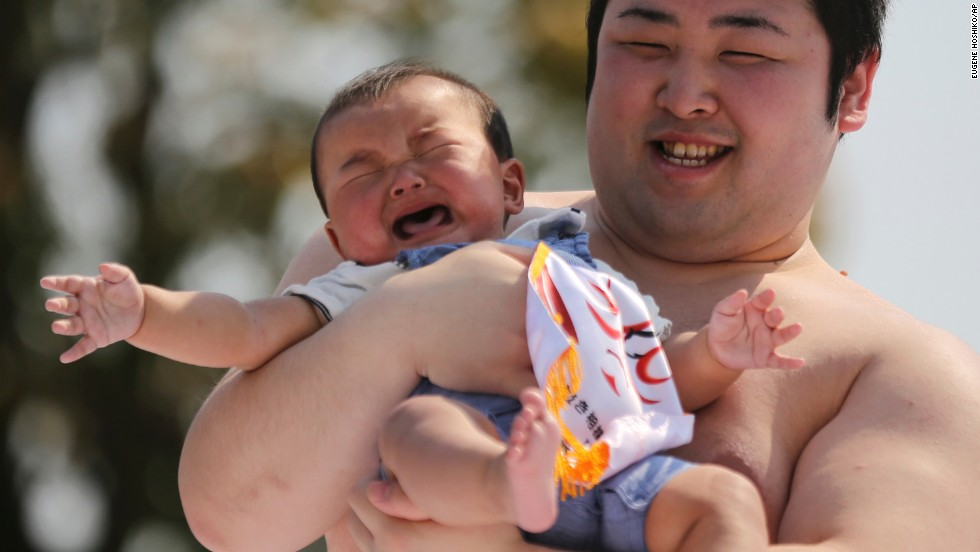 Held by an amateur sumo wrestler, a baby cries during <i>naki-zumo</i> (crying baby contest) at Sensoji Buddhist temple in Tokyo, Saturday, April 26. The contest celebrates a traditional belief that a baby who cries grows more quickly.