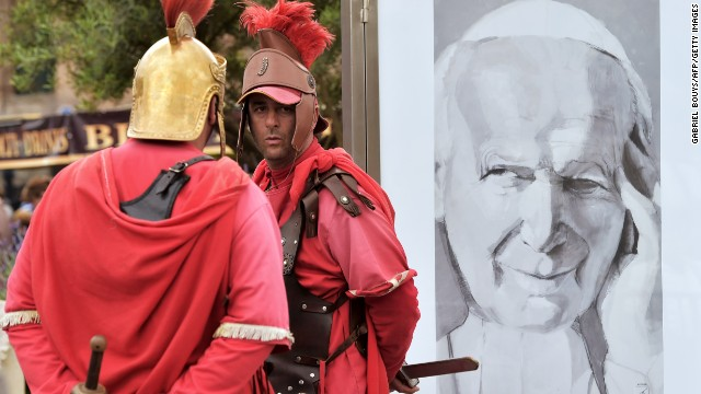 Men dressed as centurions stand by a portrait of Pope John Paul II in Rome during the canonization Mass on April 27.