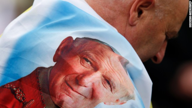 A man is wrapped in a flag bearing a picture of Pope John Paul II in St. Peter's Square.