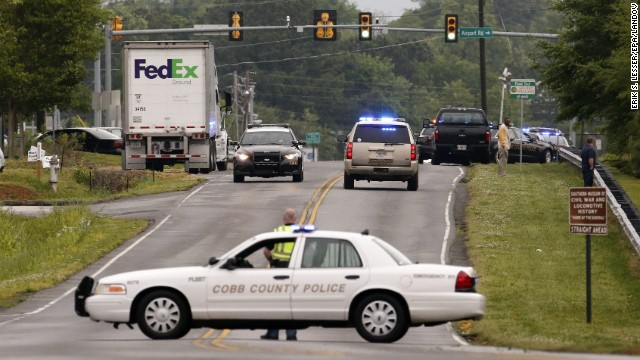 Law enforcement officers respond to shootings at a FedEx facility in Kennesaw, Georgia, on Tuesday, April 29. Police say a FedEx package handler went on a rampage Tuesday, wounding six people -- one of them critically -- before fatally shooting himself.
