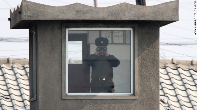 A soldier looks through binoculars inside a sentry post along the bank of the Yalu River on Monday, April 7.