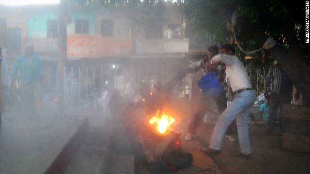 Indian bystanders attempt to douse the blaze as a local politician and a man are engulfed in flames.