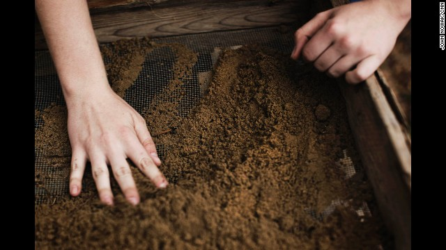 "Georgia Southern student Heather McNamee sifts dirt during an excavation dig. ""It's really hard,"" she said of locating artifacts in piles of earth. ""If you're wearing gloves, sometimes you have to take them off. It's a feeling thing."" She took part in a dig that was interrupted by rain in late March."