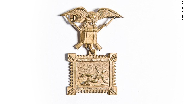 "Charles H. Knox was a corporal in Company L of the 1st Connecticut Cavalry. Captured in Virginia in his first major battle, Knox was a prisoner at Andersonville and Lawton, both in Georgia. This medal is made in the shape of a stockade with cannons at each corner surrounding the image of a Union prisoner being attacked by a guard dog. The dog is a reference to reports that the Andersonville commander used dogs to track escaped POWs. The bottom panel reads: ""Death before dishonor."" The item is in the collection of the Georgia Southern Museum."