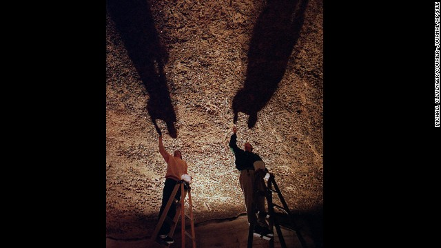 Marengo Cave visitors have tossed coins toward Penny Ceiling, where they get stuck in its soft, claylike surface. Every few years, staffers remove them, shown here.