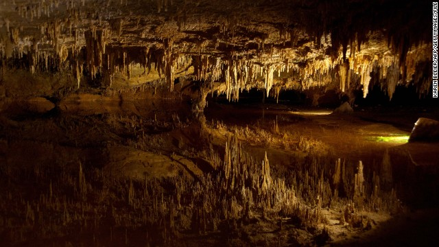 Stalactites, at top, reflect on underground pond water at Luray Caverns in Luray, Virginia.