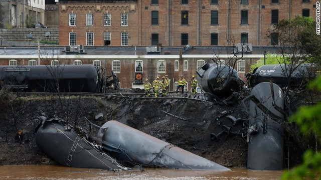 Firefighters work along the tracks where several CSX tanker cars carrying crude oil derailed and caught fire along the James River near downtown Lynchburg, Virginia, on Wednesday, April 30.