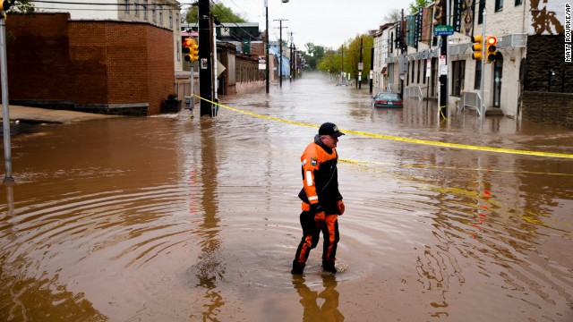 Police officer Robert Jonah walks through floodwaters in the Manayunk neighborhood of Philadelphia on Thursday, May 1. A powerful storm system, including a series of tornadoes, has claimed at least three dozen lives in several states this week.